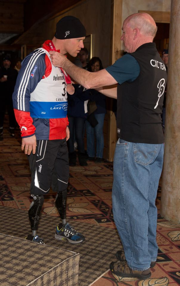 Don Becker presents a medal to U.S. Navy Lt. Dan Cnossen of U.S. Paralympics Nordic Program at the International Paralympic Committee Nordic Skiing World Cup in Cable, Wis.